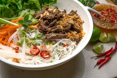 Bun Bo Xao, a zesty stir-fry of marinated beef hot from the wok paired with room temperature rice noodles, makes a satisfying main-course salad year-round. Dressed with a classic Vietnamese dipping sauce and topped with roasted peanuts, the flavors are clean, bright and restorative. (Photo: Fred R. Conrad/The New York Times)