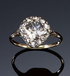 DIAMOND RING, EARLY 19TH CENTURY. The pear-shaped bezel set with a central rose-cut diamond within a surround of similarly-cut smaller diamonds