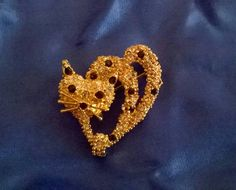 Such an unusual shape. A whimsical little leopard with a sweet expression and great whisker detail. In very good condition. Heavily gold plated. 2 and a half cm wide and tall.