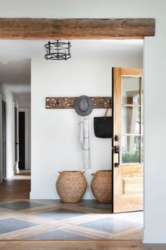 I couldn't love this natural wood filled entryway more! I love the light wood door, the woven seagrass baskets, those natural, worn wood beams and that wood and stone floor!