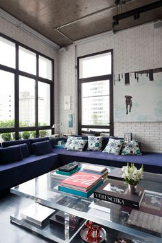 A translucent coffee table is paired with a long, purple sofa and white brick walls. Stylish books, white flowers, and a large hanging wall art make artsy additions to the urban space.