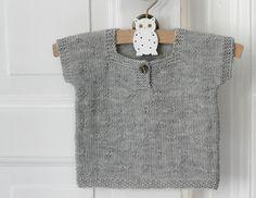 """En lille kortærmet T-shirt eller vest er suveræn som det lille """"ekstra"""" lag, når baby skal holdes varm på den lækre måde. Den lyserøde i hulstrik er strikket i bomuld/akryl og den gråmelerede i strukturmønster er i baby merinould – begge dele ultra bløde. Strikkeopskrift får du i 3 størrelser. Baby-T-shirt STR: 3/6-9/12-15/18 mdr. DET SKAL DU BRUGE: 2 ngl…"""
