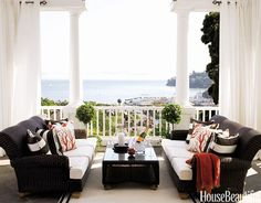 A pair of wicker sofas from Restoration Hardware suits this classic porch, which is just off this home's living room. Pillow fabrics are Stripe in Chocolate Kiss by Perennials and Mari in Coral by Lulu DK. Casual and cozy!