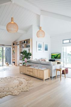 The light wood flooring and furniture goes beautifully with the white walls and ceiling and grey sofa.