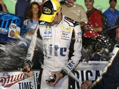 Brad Keselowski cuts his hand on a champagne bottle while celebrating in victory lane after winning the Quaker State 400 at Kentucky Speeedway in June 2014.