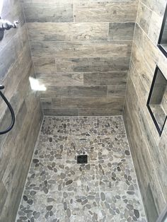 Wood look tile shower with natural pebble floor. Superior Development, Llc. Nashville builder. Design by Jessica Powers.