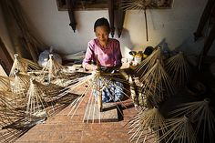 A woman makes umbrellas from bamboo using a traditional method in Shan State…
