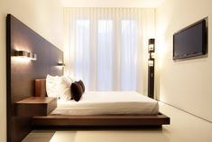 Minimal wooden bed in small bedroom