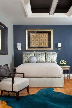 Moody blues combine with bling in this transitional guest room with glam undertones. A marine blue accent wall draws the eye to the bed, where a row of metallic pillows literally shines in the space. A modern fixture hangs from a niche in the ceiling, which is painted a rich, dark brown for added interest.