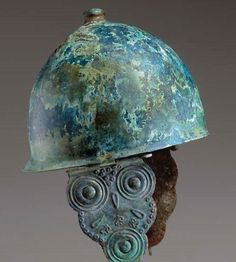 Etruscan Montefortino helmet, 4th-3rd century B.C. Of domed form, the rim turned out and further peaked at the rear, riveted at the center with two hinged loops preserved on the interior, the crown topped by a knob finial with a central depression, the separately-made cheek-pieces attached by means of hinges riveted to each side and secured by a long pin with a disk-shaped terminal, each cheek-piece with a scalloped outline, 30 cm high. Private collection, from Christie's auction