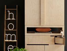 meuble de rangement en beige, avec des tiroirs coulissants, pot plante verte recouvert de rotin en nuances grises, parquet beige PVC