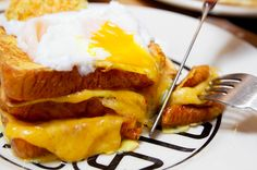 Double Decker French Toast Grilled Cheese Sandwich Topped and Filled with Poached Eggs