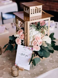 Fill gold lanterns with flowers, like this one brimming with roses for a wedding centerpiece that will light up the night. #weddingflowers