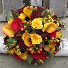 Hand tied bouquet created with flame calla lilies, red roses, burgundy roses, leucadendron, kangaroo paws, orange hypericum berries, yellow spray roses, bee balm pods, and baby seeded eucalyptus. #blossomandbasketboutique