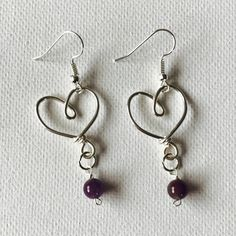 Made a pair of silver wire heart dangling earrings with Amethyst beads!