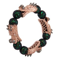 Inlay work is thousands of years old and Lotus Arts de Vivre uses scarab wings inlaid in ebony wood to create this magical design. The wood wears so beautifully and seems to release power and wellness into the skin of the owner. This bracelet took approximately 10-12 weeks of labor to create.  The dragon heads are made of sterling silver plated with 9K pink gold set with ice diamonds.