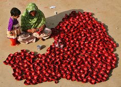 A woman paints dried clay lamps at her workplace as her daughter watches on the outskirts of Jammu, Indian-Administered Kashmir.