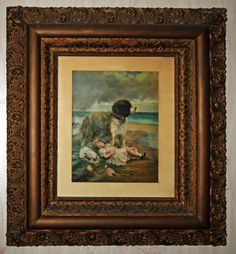 Antique print and frame of a St. Bernard dog protecting a little girl taking a nap by the sea side.