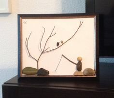 One of a kind framed pebble art depicting a fisherman fishing in a river with an over stretched tree branch harbor in two perched birds. Picture