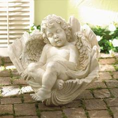 Sleeping cherub in shell garden statue