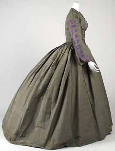Afternoon dress, silk, 1860's. Grey with purple accents, side view revealing trim on sleeve, could very well be a half mourning outfit. In storage at the Met