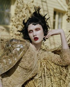 I see a combination of my favorites: pale skin, red lips, ebony hair against the gold, Floria Sigismondi quasi Tim Walker quasi Tim Burton quasi etc . . . all in one.  By Tim Walker.