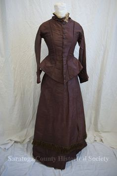 Burgundy taffeta bodice. Ruffled collar with layer of lace. Cuffs are ruffled. Round, flat, fabreic covered buttons run the length of the jacket. The back is darted and longer in the middle. Saratoga County Historical Society