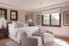 Understated neutrals create a soothing retreat in a bedroom with a tufted bed. A beautiful area rug adds a level – and layer – of sophistication to the neutral room, while a small chairs add additional seating.