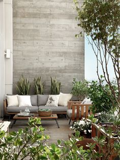 Terrace with potted trees. Lovely except I'd switch out the uninviting sharp blade plants right behind the sitting area.