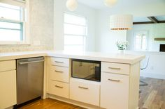 A kitchen in suburban Detroit uses modern slab-style cabinets with traditional touches to achieve a very inviting and warm feel. Warm Kitchen, New Kitchen, Brass Kitchen, Kitchen Ideas, 1960s Kitchen, Mid Century Modern Kitchen, Kitchen Shelves, Kitchen Cabinets