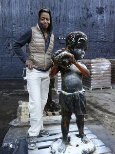 Kara Walker ao lado de sua instalação, construída no interior da antiga fábrica da Domino Sugar, em Nova York. Walker, uma artista conhecida pelas silhuetas que invocam questões de história, raça e poder, criou uma enorme escultura em forma de esfinge coberta com açúcar — uma ode ao trabalho dos negros nas plantações de açúcar. (Abe Frajndlich/The New York Times)