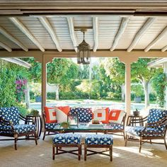 Deep navy and pops of bright orange create an inviting outdoor atmosphere.  Vintage bamboo furniture gets revived with cushions covered in a geometric print. coastalliving.com