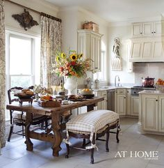 Cozy Canadian Cottage.  Curtains hung high with wooden carving above window.  Table. Bench with checked cushion.  White on White with natural brown.  Do not like glaze on cabinets.
