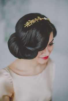 Voluminous updo on brunette bride with golden crown.