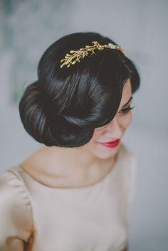 Voluminous updo on brunette bride with golden crown.