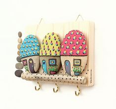 Wall hanging key with painted stones applied on reclaimed wood. Funny and lovely homeware There are 3 hooks below the houses useful for hanging keys, jewelry and other small items. A final coat of varnish protects the color. Measure: 14x11x2 cm approx. - weight (packaging included): 450