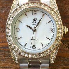 Rachel Zoe Stainless Steele everyday watch This beautiful designer watch matches everything and is soooo comfortable (most watches bug me due to their weight!). Sparkling, understated, diamond-looking stones with subtle mother of pearl face. Band is matte on outside links and with slight shine on inside links - which have a slight hint of rose gold. See pics for minor wear and tear. Rachel Zoe Accessories Watches