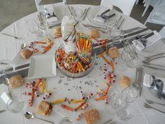 Voici une table idéale pour les enfants! Vos petits pourront apprécier la soirée en trouvant des carambars et des malabars en guise de décoration. Le centre de table n'est autre qu'une vasque et des cylindres remplis de sucreries et d'orchidées. Quelques pépites et granulats argentés viennent s'ajouter à la décoration.