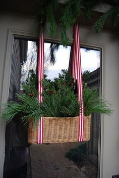 Hang basket by two lengths of ribbon on door. Fill with evergreen clippings and Christmas decorations. Great substitute for a Christmas wreath.