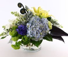 Rhapsody In Blue - Let this beautiful bouquet send your message. The combination of blues, chartreuse, yellows and white creates an appealing combination. #KittelbergerFlorist #RochesterFlowers