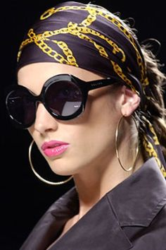 Big round silver hoop earrings, big shiny black rounded sunglasses, gold chain print on a black silk scarf tied as a head wrap, & a shocking. Trend Fashion, Fashion Show, Oh Sheila, Mode Turban, Hair Scarf Styles, Black Round Sunglasses, Bandana Hairstyles, Turban Style, Hair Accessories