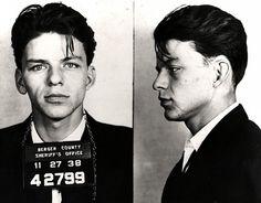 """A prisão de Frank Sinatra  Em 1938, Frank Sinatra foi preso aos 23 anos de idade, quando ainda não era famoso. Na foto, Sinatra aparece sendo fichado em uma delegacia de Nova Jersey antes de ser solto, depois de pagar fiança. A acusação era de que ele teria feito sexo com uma jovem """"solteira e de boa reputação"""", sob promessa de casamento. Um mês depois se descobriu que a moça era casada, e o processo acabou sendo arquivado"""