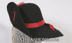 The base pirate hat that Costandina be wearing is the Swashbuckler hat in black wool for $65. Her version has burgundy hat edging and silver trim added, as well as a trimmed hat pin and finish feather bundle fer a total cost of about $155. Arrrr hats can be customized in hundreds of different ways.