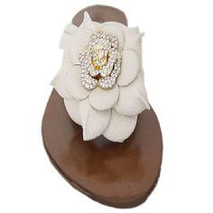 Rasteira Next Wet White - Mezzo Punto  Rasteirinha com forro em couro cor chocolate.  Tiras em couro na cor off white.  Enfeite em couro com formato de pétalas e metal cravejado em cristais em formato de um botão de flor.  Solado de borracha.  A Mezzo Punto é uma marca de calçados femininos de altíssima qualidade e sofisticação. Sua linha é ideal para gestantes e recém mamães, pois os sapatos são produzidos com couros e materiais extremamente flexíveis para poder calçar confortavelmente os…