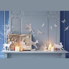 un livre de contes réalisé en cartonnage en trompe l'œil avec des animaux , un château et un personnage qui sortent des pages et accrochés sur un mur gris bleu.