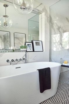 Ali Budd Interiors - Modern black and white bathroom is fitted with black and white floor tiles placed beneath a modern oval freestanding tub paired with a polished nickel tub filler mounted to a marble slab backsplash.