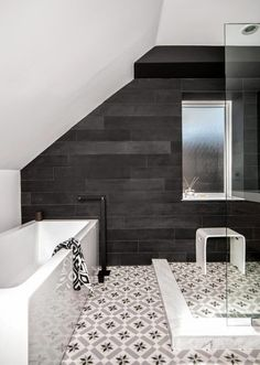 Tile a black wall - Love the look in this bathroom with the cement tiles on the floor, white walls all around and the feature black wall with large field tiles.