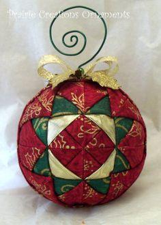 Une mini couette motif dans un patchwork de tissus de Noël avec une couche de métallisé or rend cet ornement un standout inhabituel dans votre collection d'ornement matelassé. Le motif de triangles et des carrés est travaillé avec des tissus verts, rouges, avec des accents métalliques et vif métallisé or. Il est surmonté d'un arc d'or, feuilles de houx or et un tourbillon de fil pour le cintre.  Matelassé ornements sont un excellent moyen de promouvoir un thème pour votre décor des fêtes ou…