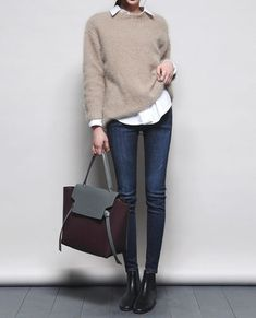 Picture Of a casual Friday look with a white shirt, a beige sweater, navy skinnies, black booties and a burgundy bag