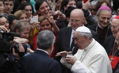 Pope Francis receives a cup of Mate, a herbal tea they drink in Argentina while visiting one of the poorest sections of Rome